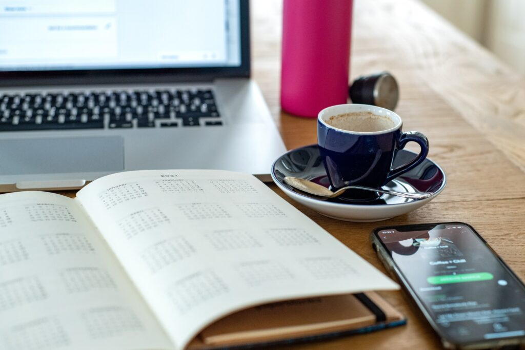 planner, phone, water and coffee in front of laptop